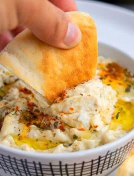 Pita Bread Being Dipped in Baba Ganoush