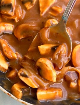 Spoonful of Easy Homemade Mushroom Gravy in Black Pot