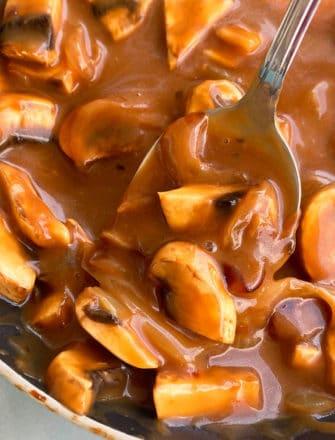 Spoonful of Easy Homemade Mushroom Gravy in Black Pot