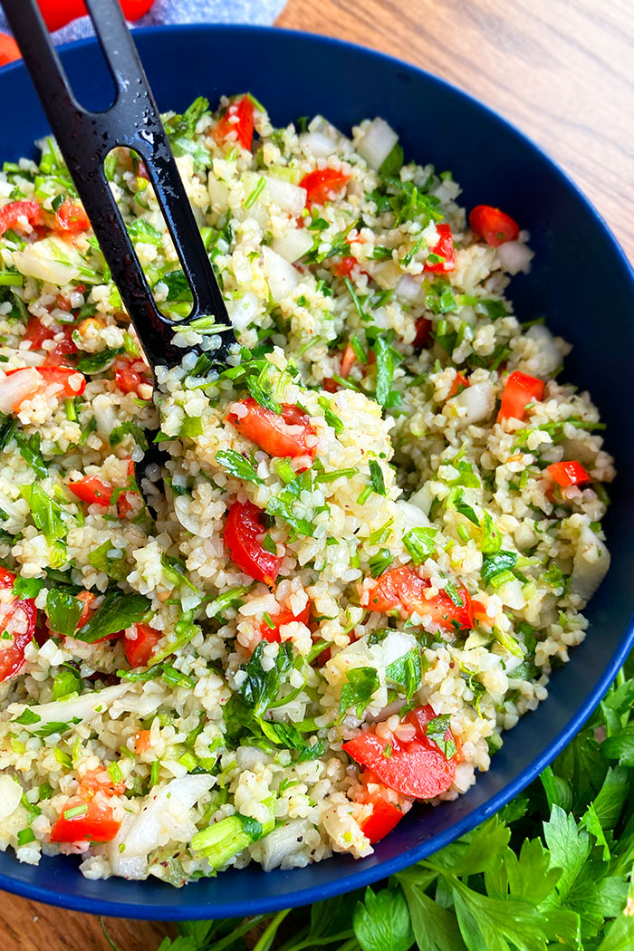 Spoonful of Easy Homemade Tabbouleh Salad in Blue Bowl