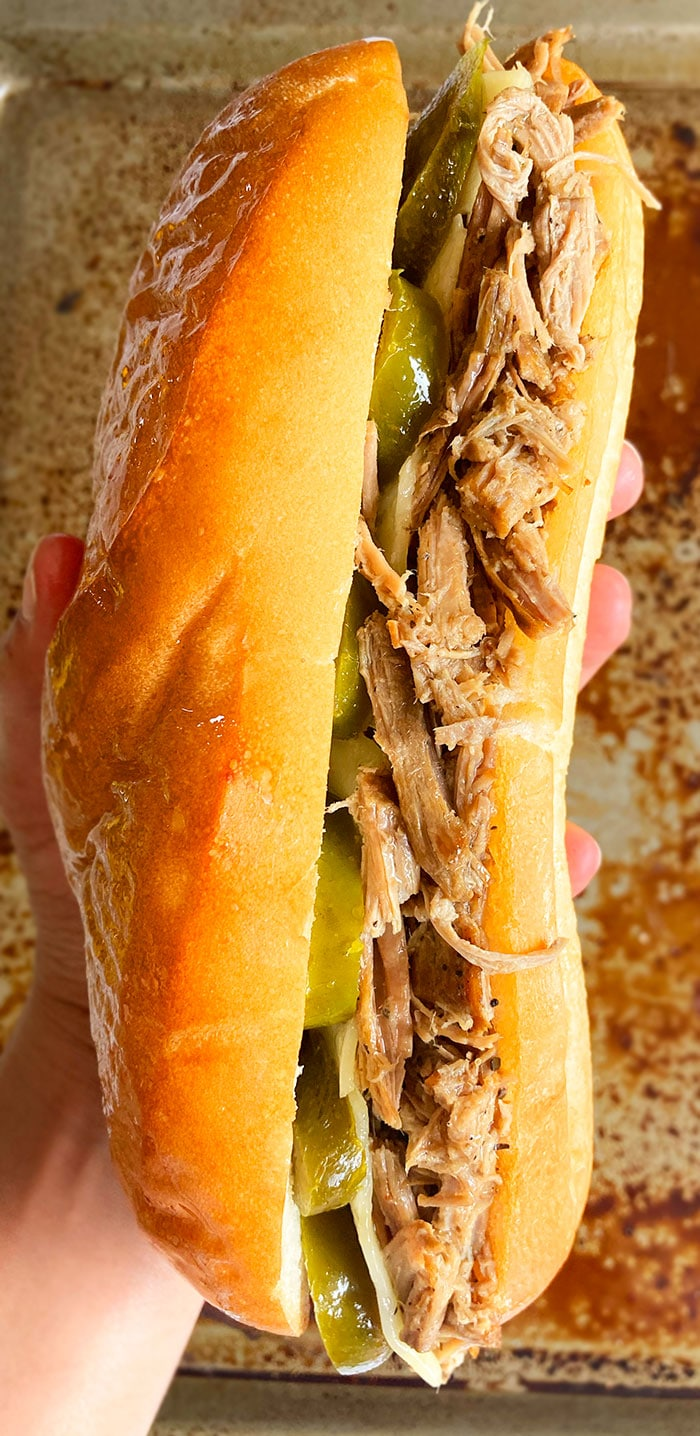 Closeup Shot of Holding a Homemade French Dip Sandwich in Hands on a Rustic Background