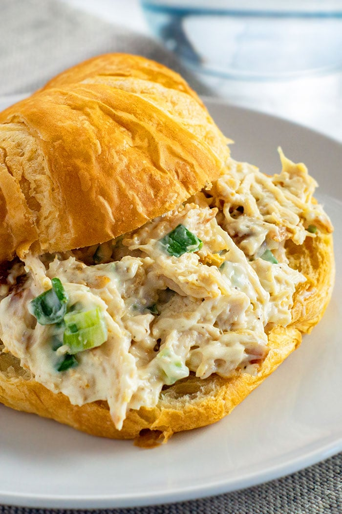 Easy Creamy Homemade Turkey Salad Filled in Croissant on White Plate