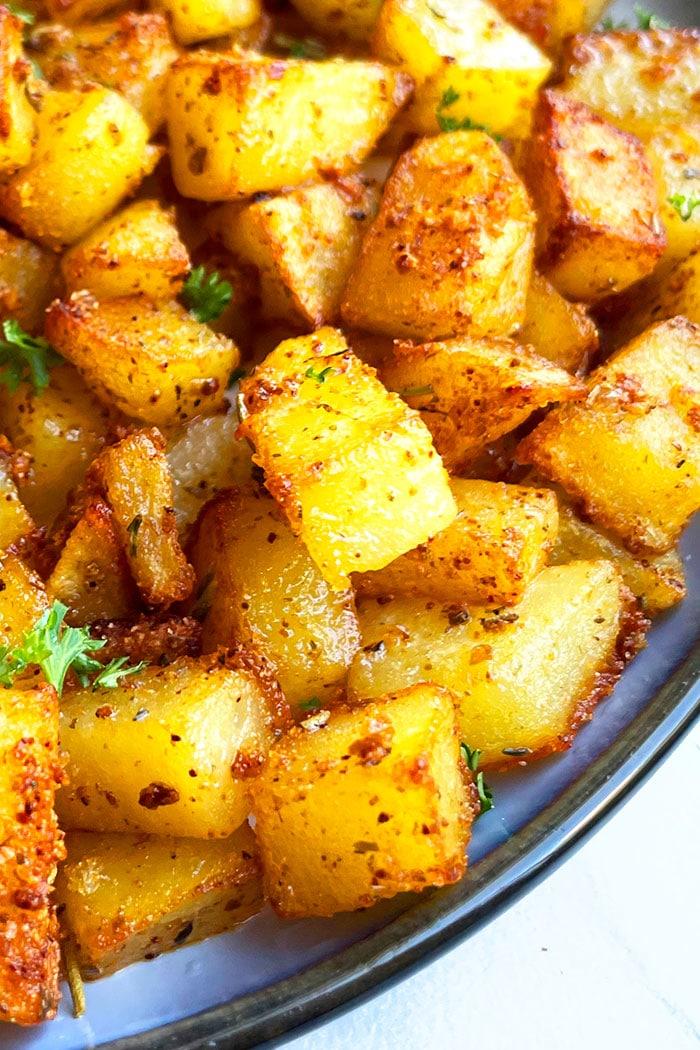Best Roasted Homemade Seasoned Potatoes For Breakfast in Navy Blue Plate- Angled Shot