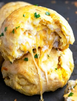 Stack of Two Stuffed Cheese Bombs on Black Baking Tray With Cheese Melting Out