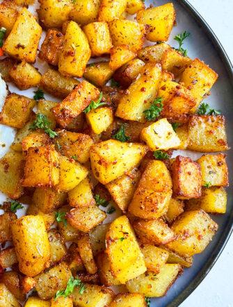 Easy Crispy Oven Baked Breakfast Potatoes in Navy Blue Plate on White Background