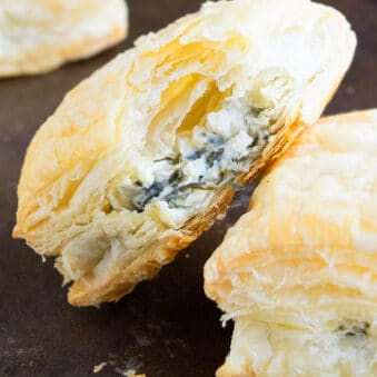 Easy Spinach Puffs With Partial Bite Removed on Black Tray