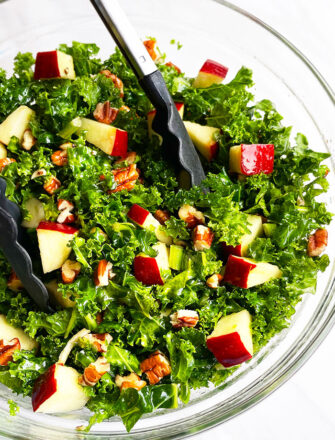 Easy Massaged Kale Salad in Glass Bowl With Tongs- Overhead Shot