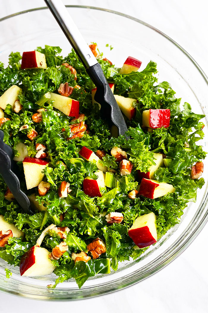 Easy Kale Apple Salad in Glass Bowl With Tongs- Overhead Shot
