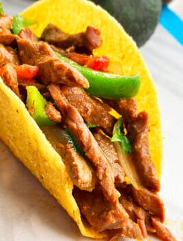 Instant Pot Flank Steak Tacos in Hard Tortilla Shell on White Background