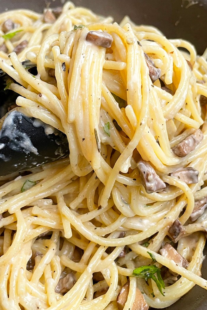 Closeup Shot of Tongs Full of Easy Spaghetti With Cheesy Mushroom Pasta Sauce