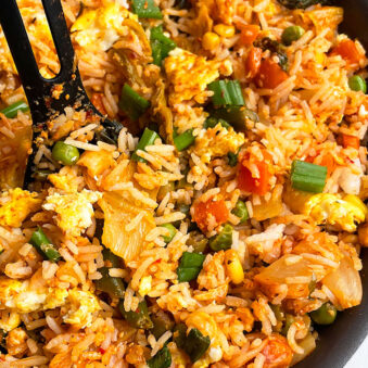 Easy Homemade Kimchi Fried Rice in Black Nonstick Pan With Black Spoon