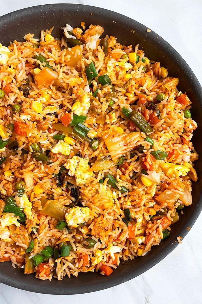 Korean Fried Rice in Black Nonstick Pot on White Background- Overhead Shot