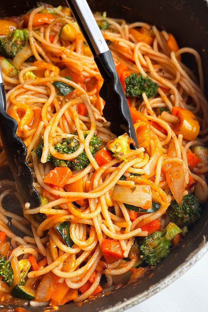 Tongs Holding Easy Vegetable Pasta in Black Pot