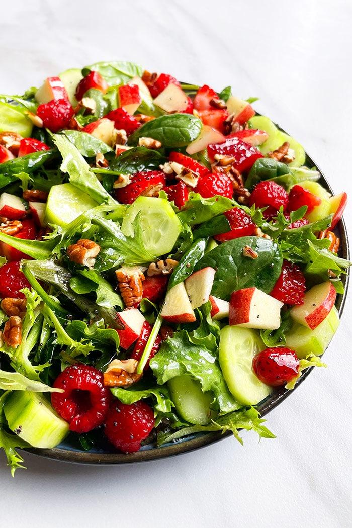 Homemade Salad With Orange Vinaigrette in Black Plate on White Background