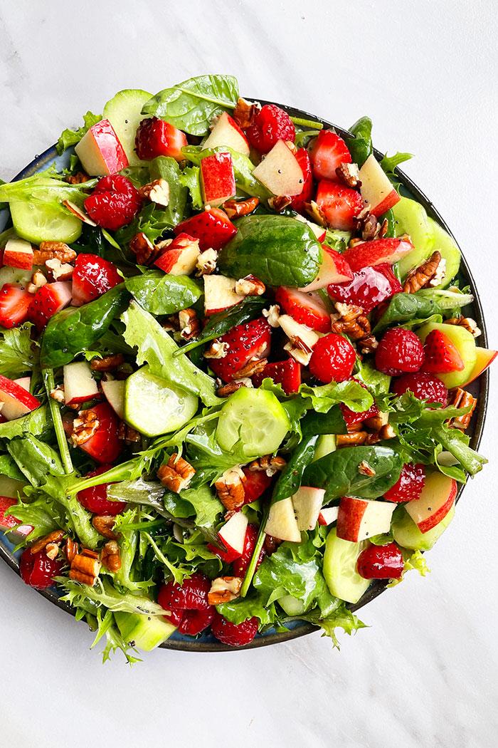 Best Summer Salad in Black Plate on White Background