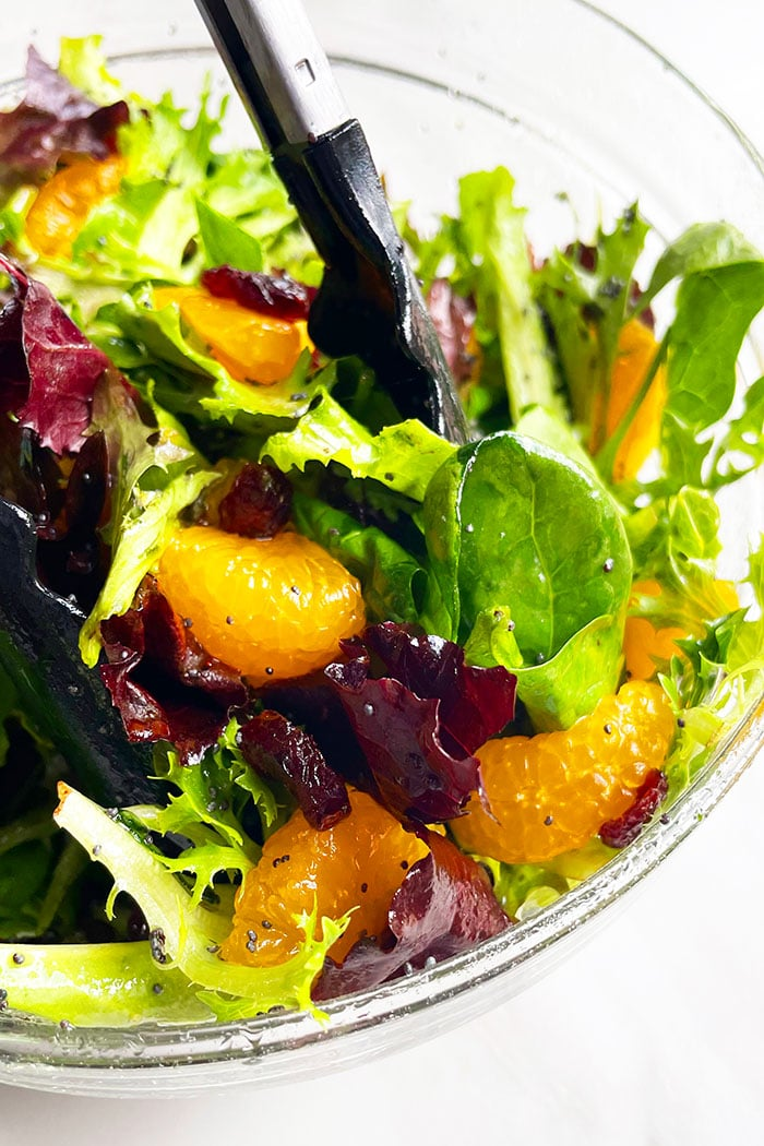 Tongs Full of Classic Arugula Spinach Orange Salad With Orange Dressing and Cranberries in Glass Bowl