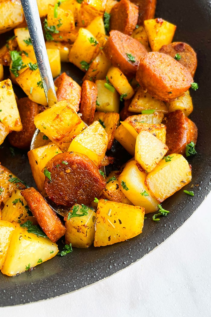 Crispy Potatoes With Sausages in a Spoon- Angled Shot