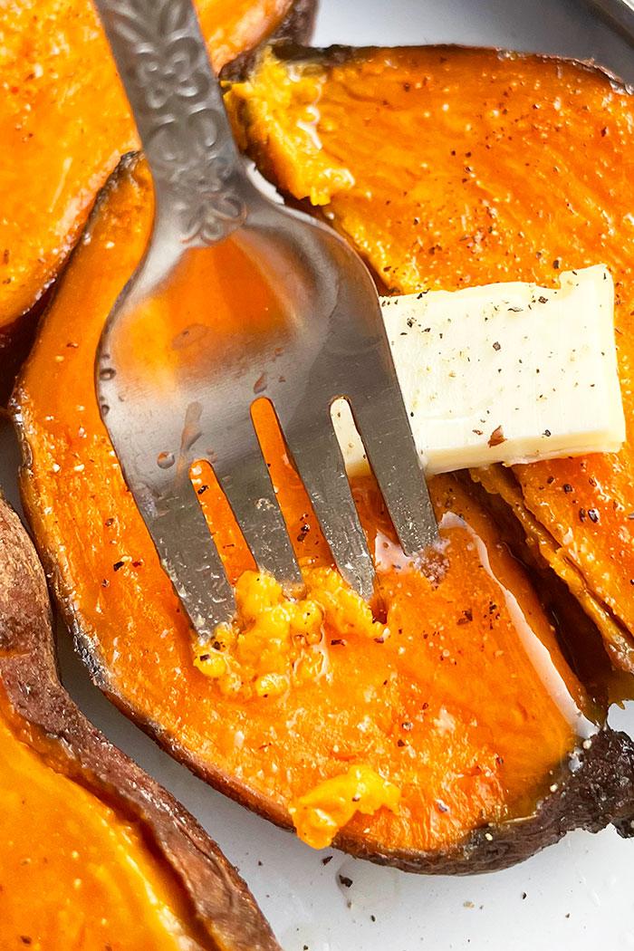 Fork Full of Tender Sweet Potato Flesh With Butter, Salt and Pepper- Closeup Shot