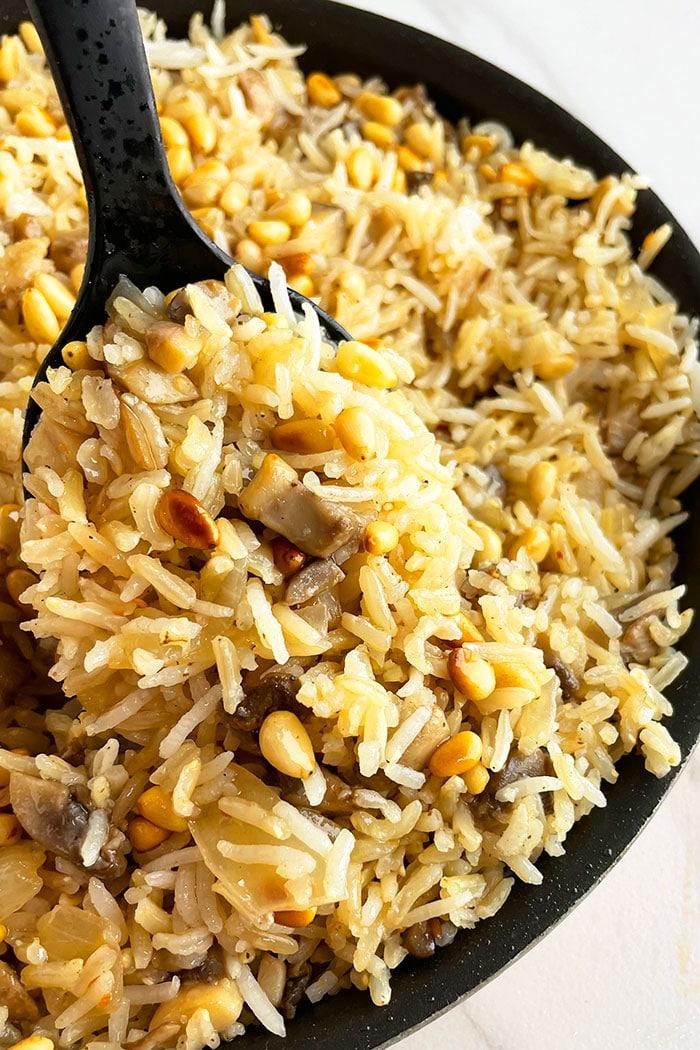 Spoonful of Mushroom Rice Pilaf in Black Pot- Closeup Shot