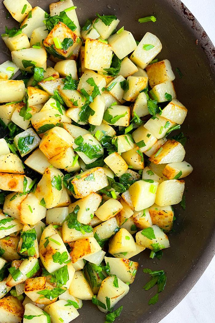 Easy Lemon Garlic Parsley Potatoes in Black Pan Made on Stovetop- Overhead Shot