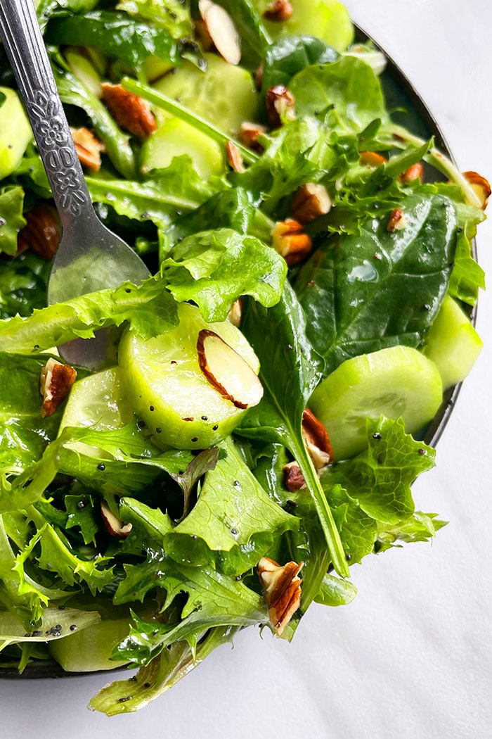 Fork Full of Simple Mixed Salad With Almonds and Pecans